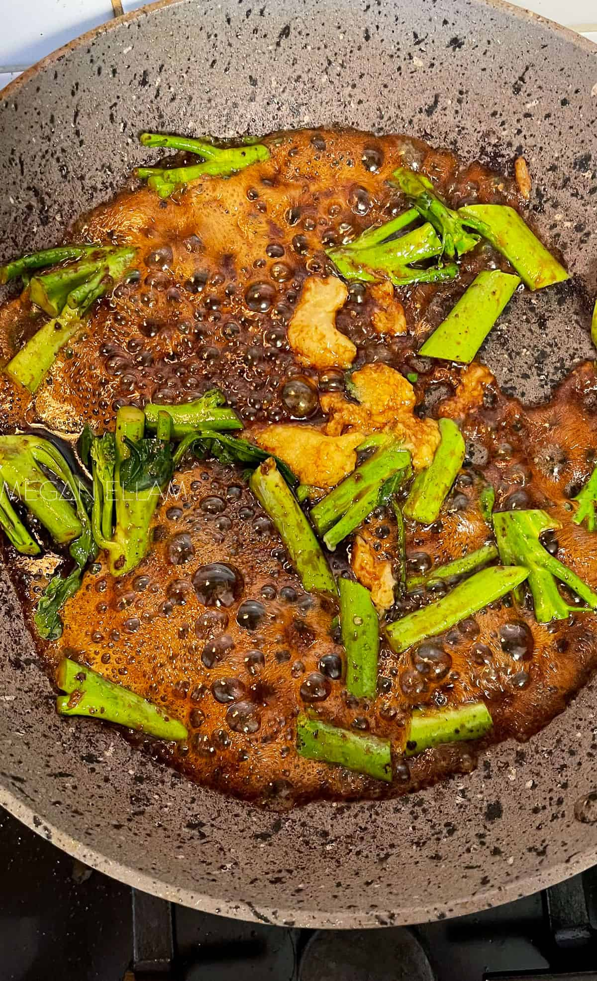 a frying pan with broccoli and sauce in it.