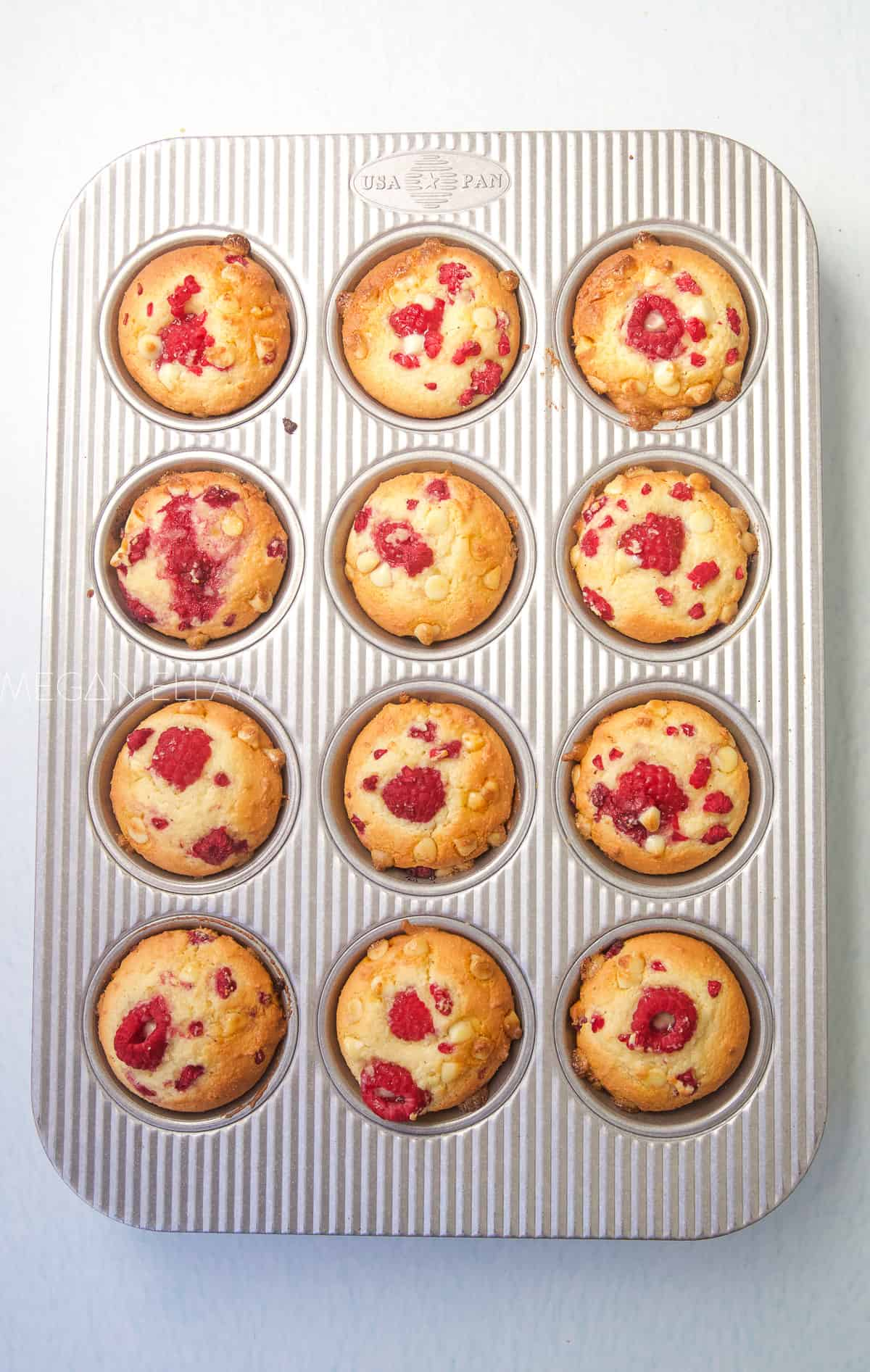 Baked raspberry muffins in a baking tray.