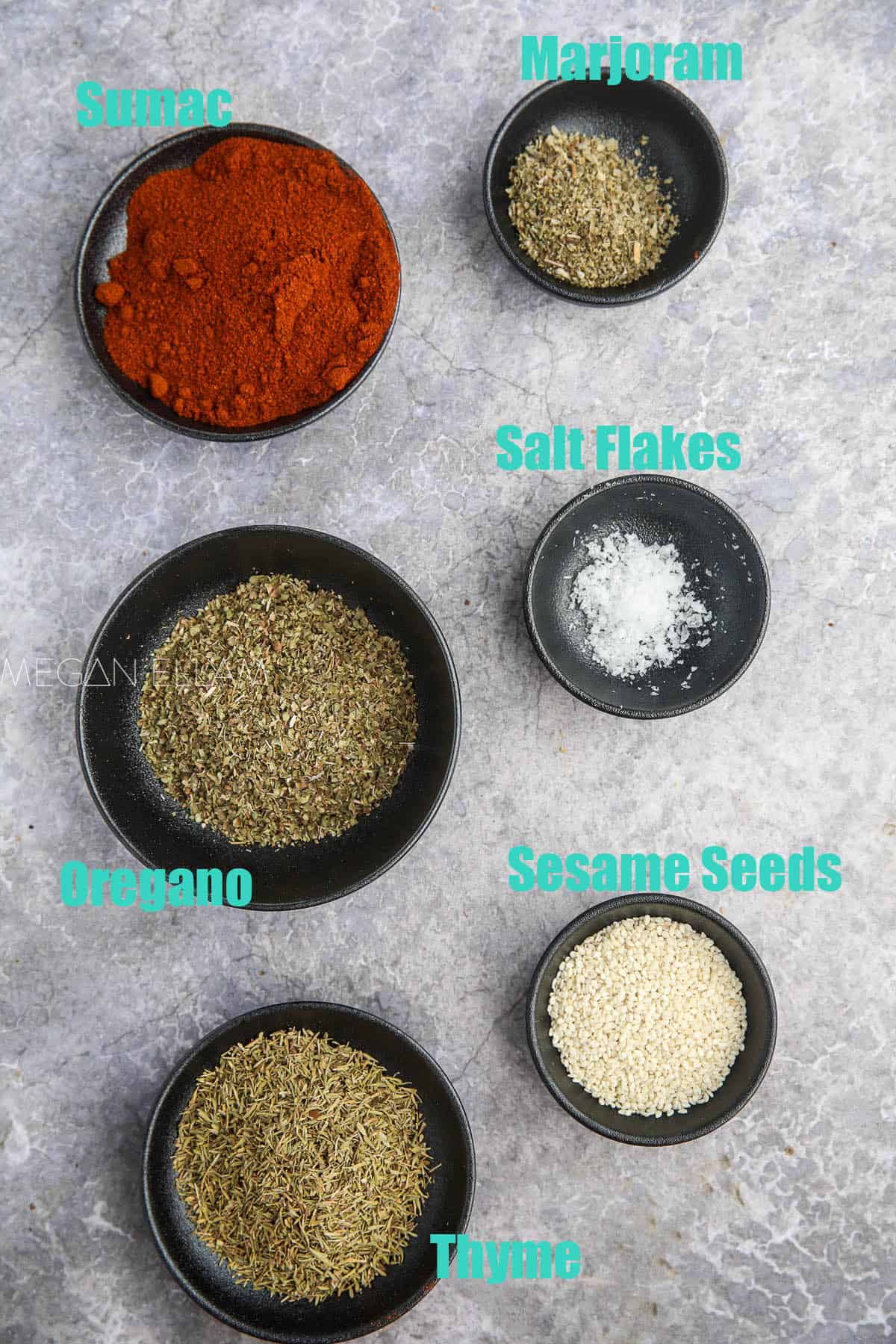 Za'atar spice ingredients in small bowls.