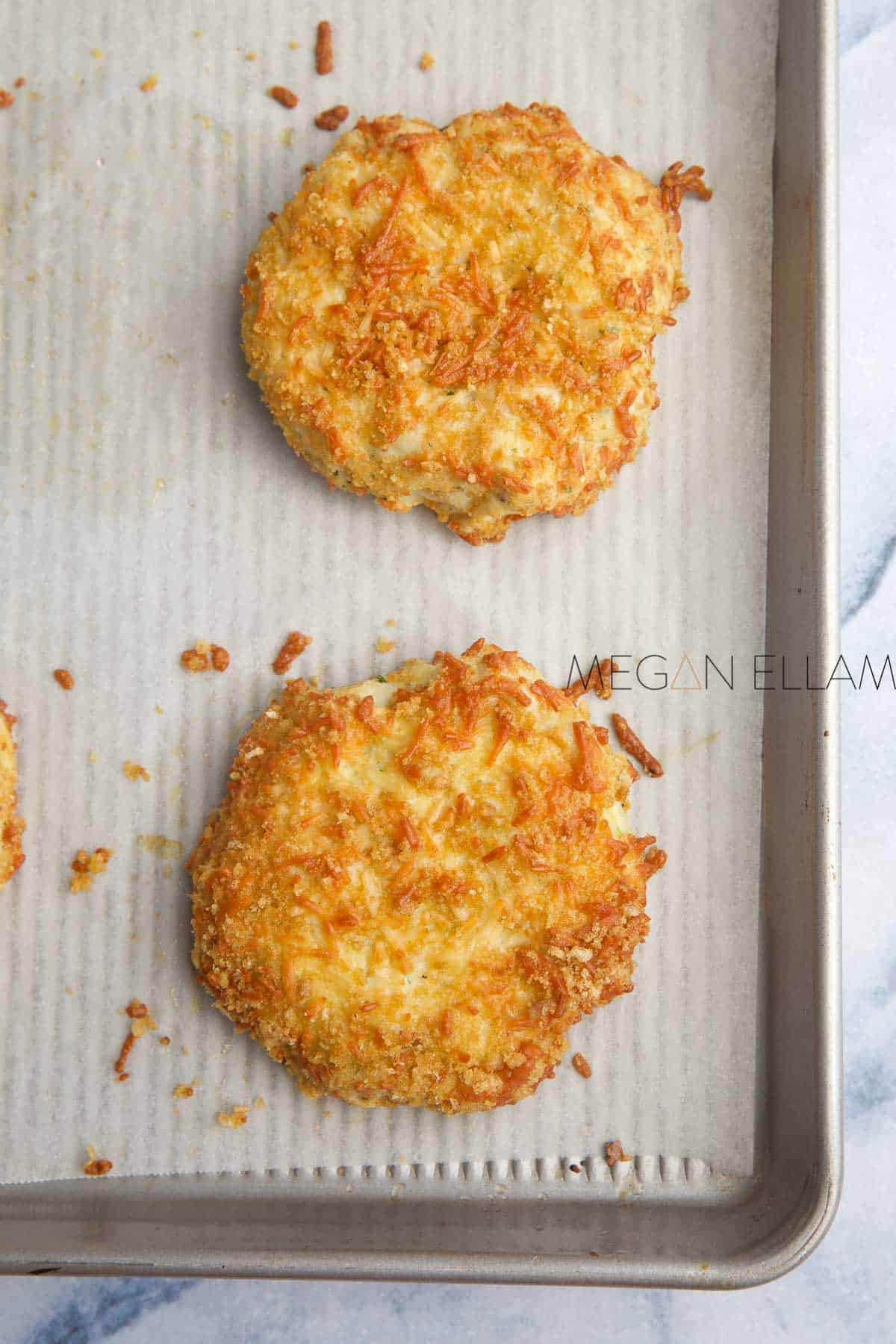 two keto fish cakes with a crispy coating on a lined baking tray