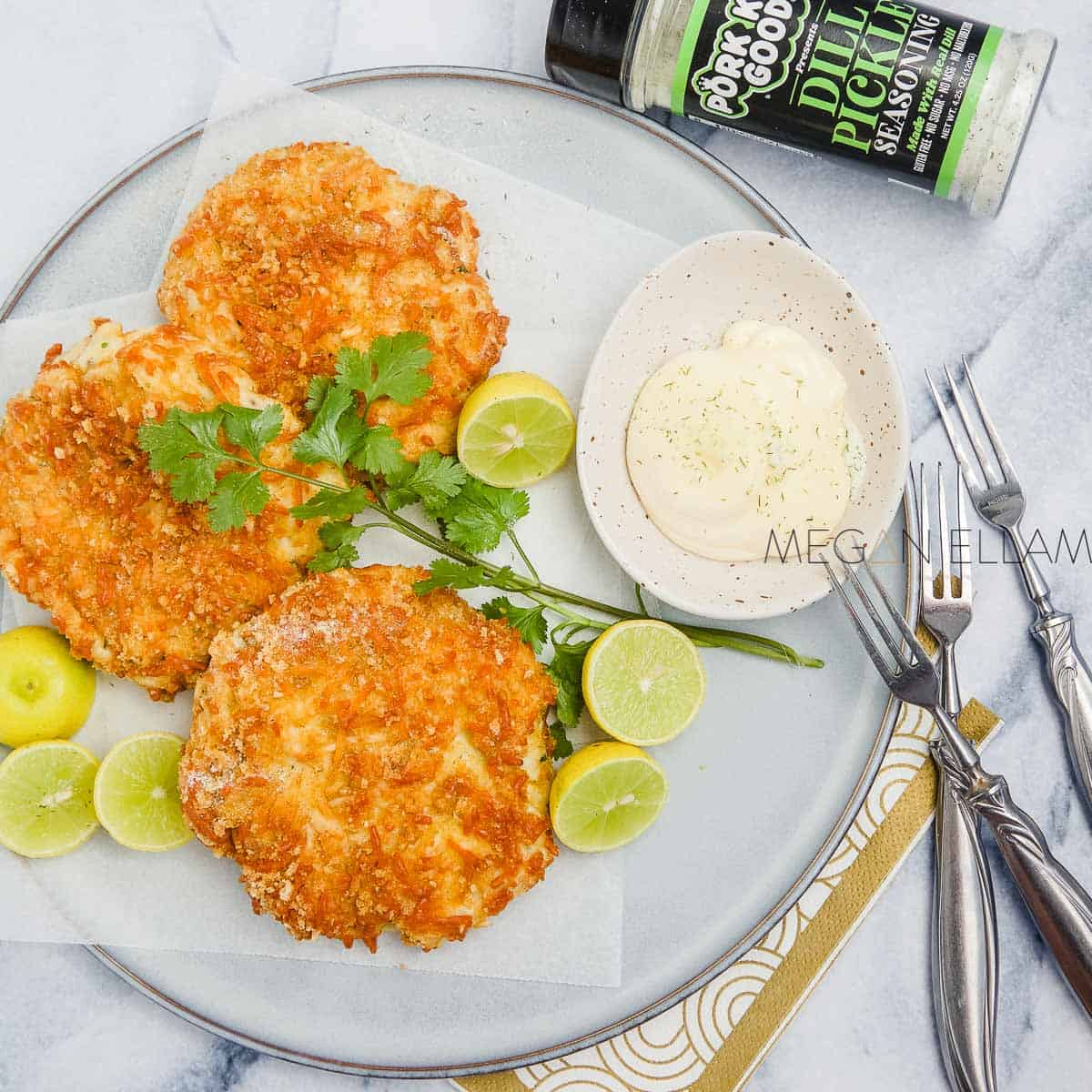 a plate with keto fish cakes, halved limes, tartare sauce with seafood forks beside it