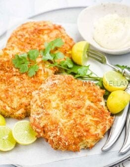 Fish cakes on a plate with tartare sauce, lime halves and seafood forks
