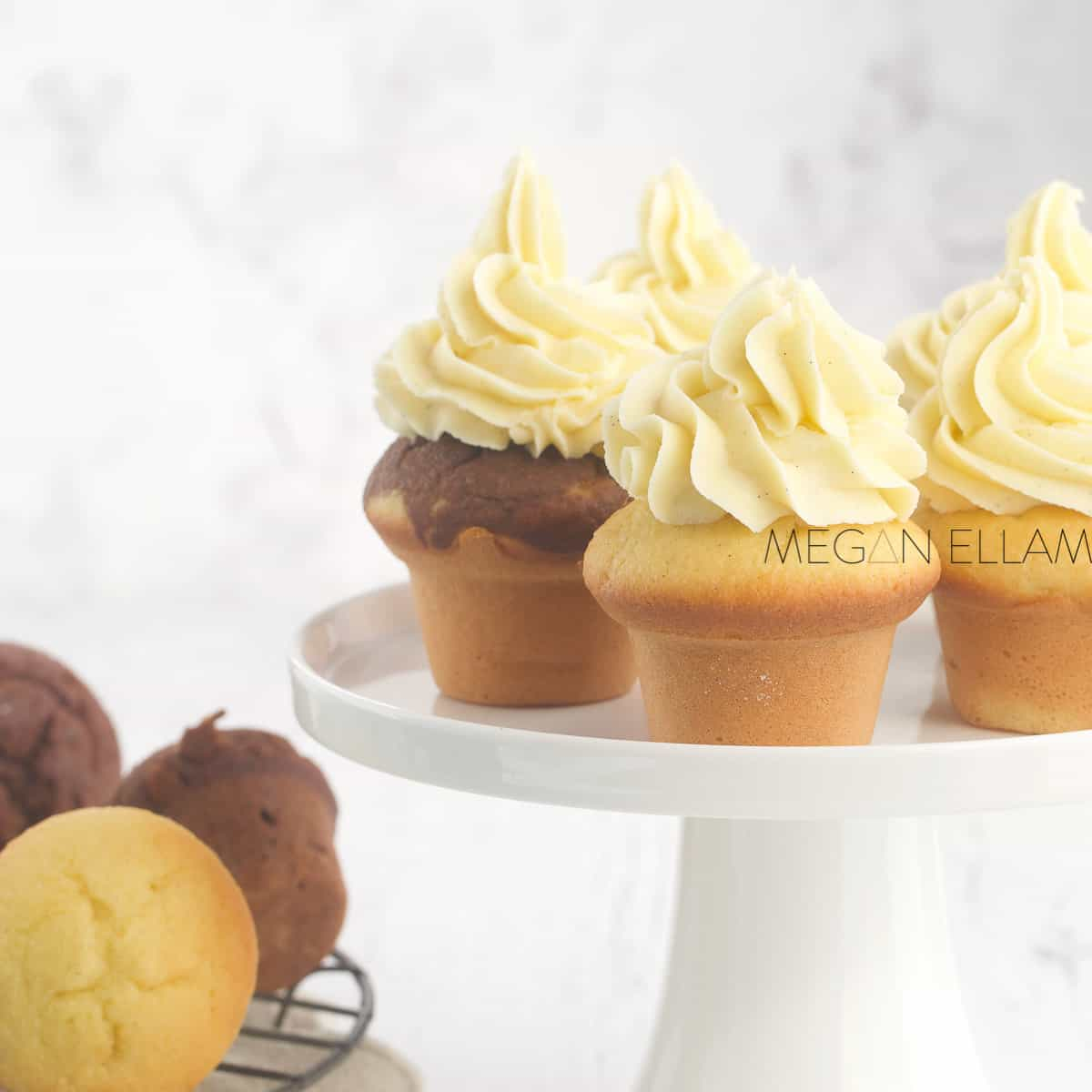 Keto cupcakes with vanilla frosting on a stand.