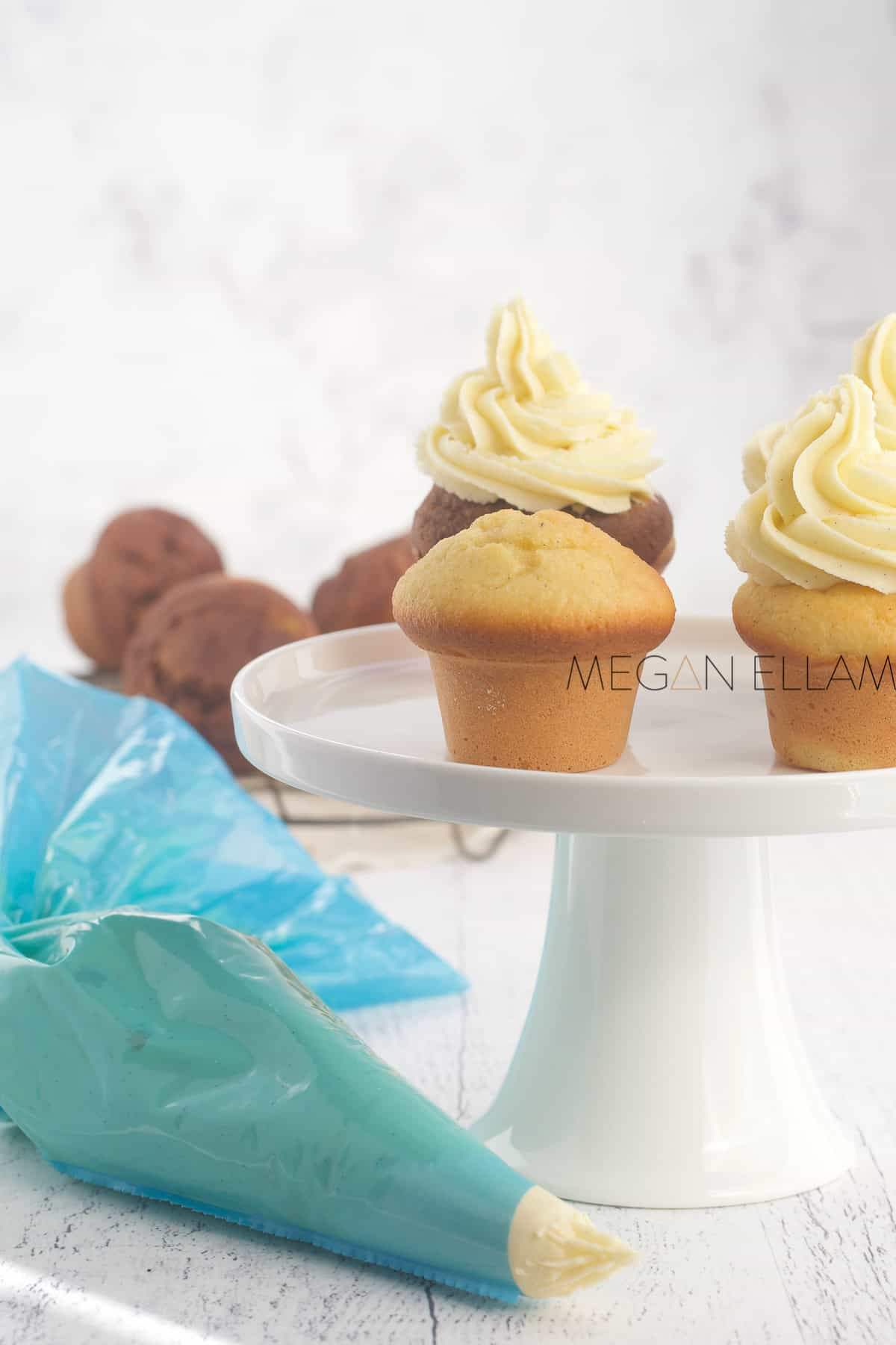 Iced cupcakes on a white cake stand.