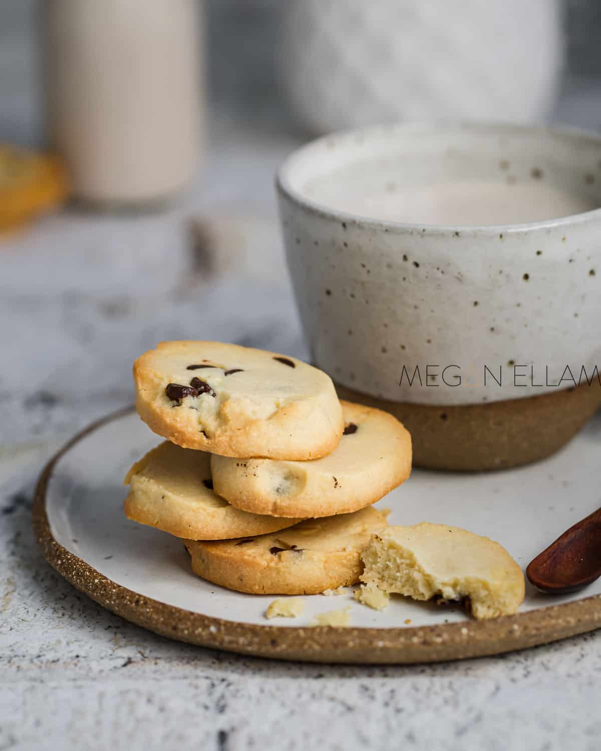 Almond flour cookies on a plate with a cup of tea.