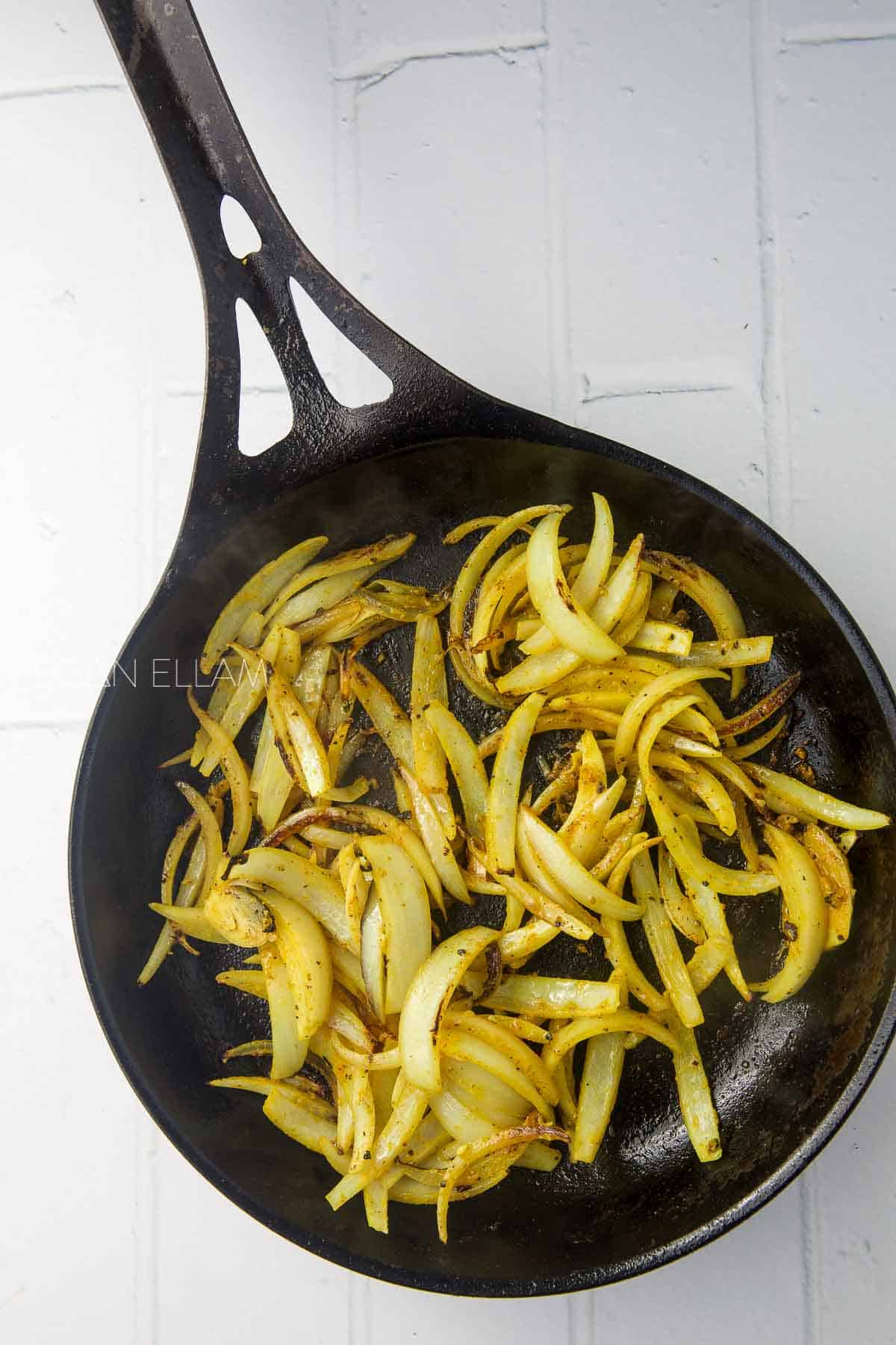 Onions frying in a cast iron pan.