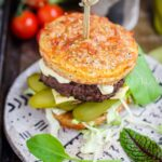A burger and salad on a grey plate.