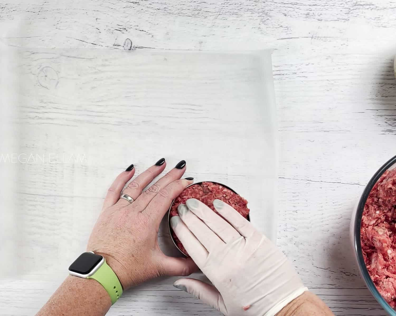 A gloved hand shaping a burger.