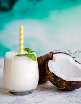 A shake and a coconut on a kitchen benchtop.
