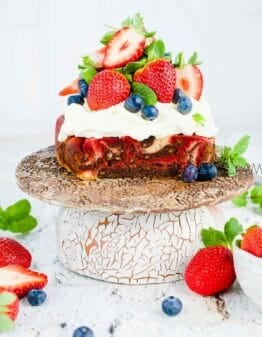 Marbled Mud Cake with whipped cream and berries on top.