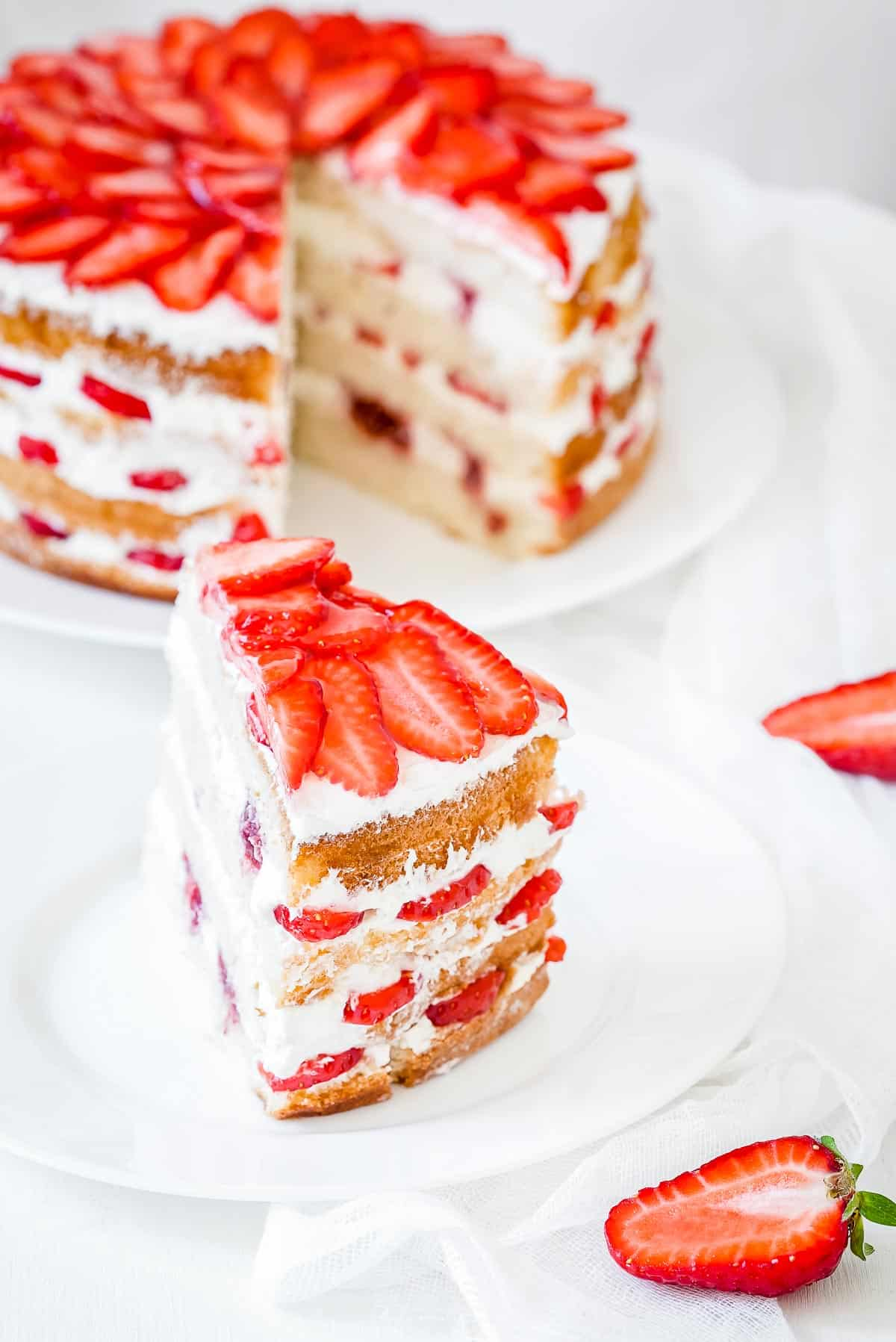A strawberry shortcake with a piece cut out of it.