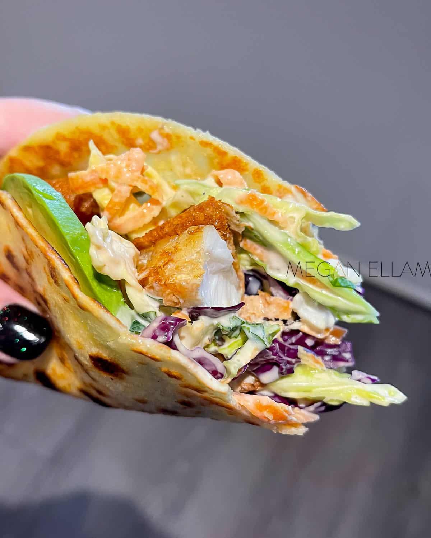 A fush taco in a hand.