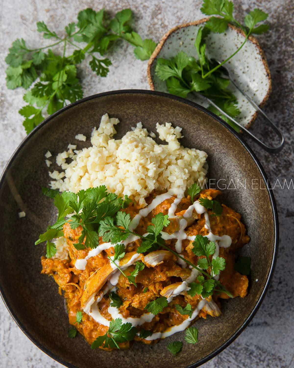 Brown bowl with butter chicken and rice in it.
