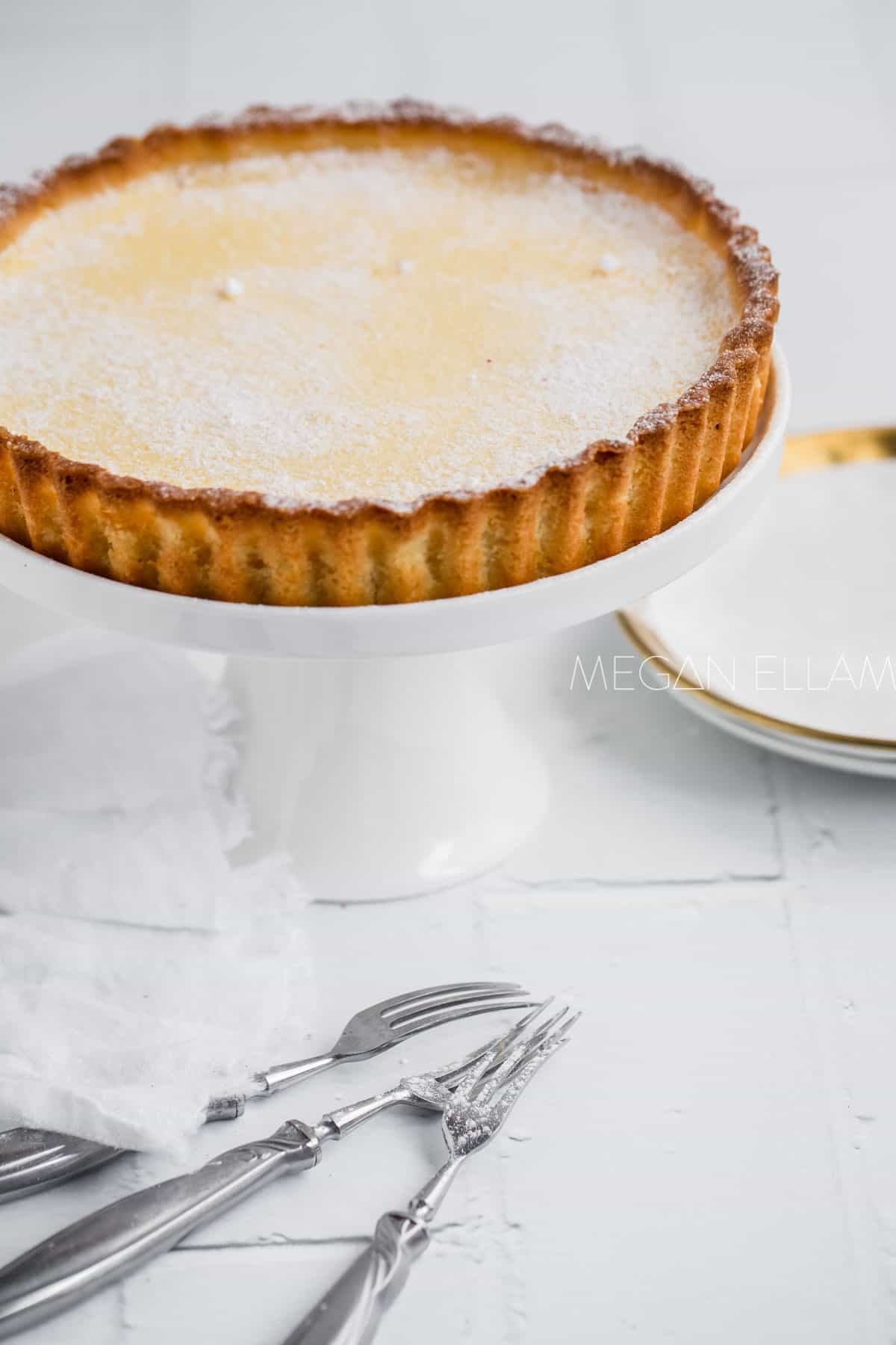 Almond flour pie crust filled with custard on a cake stand.