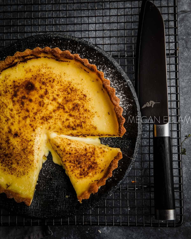 Bruleed Tart on a black plate.
