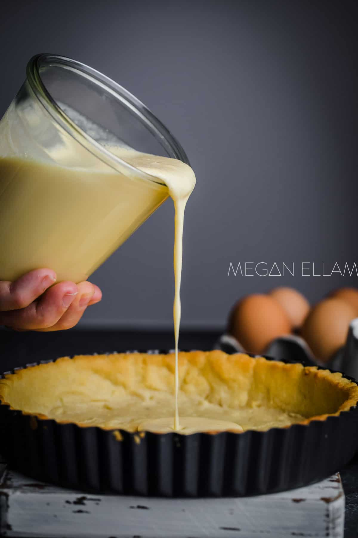 Keto custard being poured into a pie shell.
