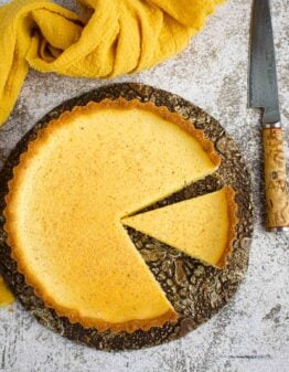 A custard pie with two slices cut out of it.